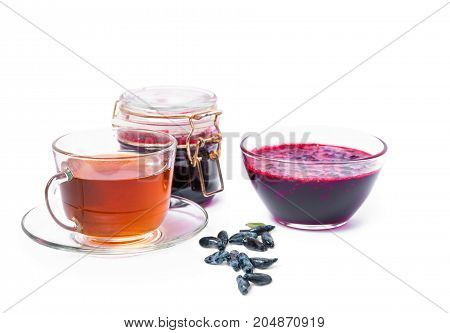 Jam with honeysuckle blue honeysuckle berries and tea in a glass container isolated on white background