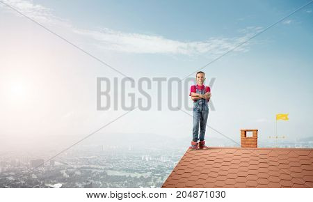 Cute kid girl standing on house brick roof with hands crossed on chest