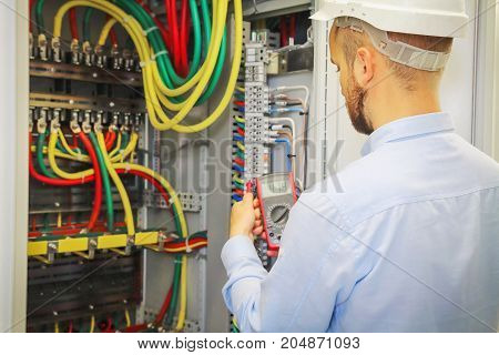 electrical engineer with multimeter on background of distribution cabinet of electrical power cables.