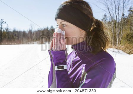 A Woman blowing her nose outside in the cold