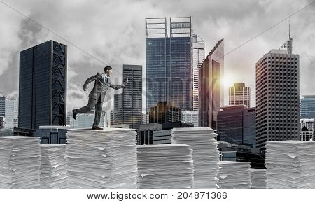 Businessman in suit running with phone in hand on pile of documents with sunlight and cityscape on background. Mixed media.