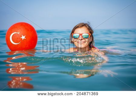 Young girl swims in blue water at sea with a turkish flag depicted on a balloon. Sea beach vacation in Turkey. Smiling girl on sea