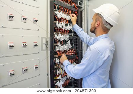 Service Engineer adjusts equipment in data center. Server room of datacenter.
