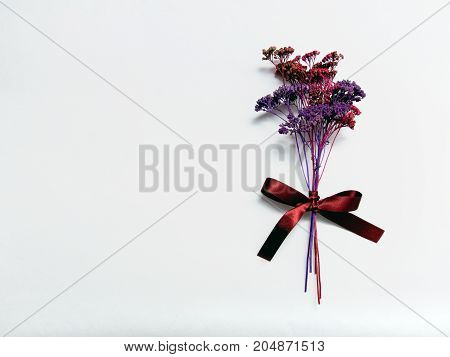 Dry flowers Flat lay Bouquet of dried flowers of purple and red color tied with burgundy ribbon on white background Photo template with space for text