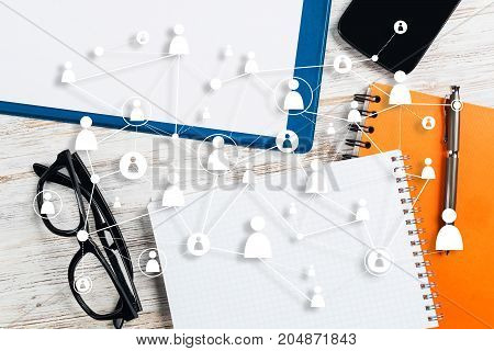 Top view of modern workplace with office stuff and social network connection above presenting still office life. Mixed media.