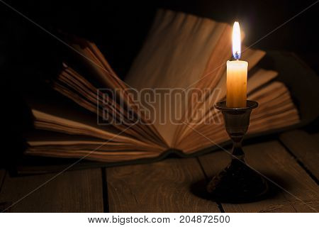 Old antique magic book opened with burning candle near on the wooden table.