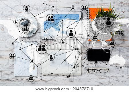 Top view of modern workplace with office stuff and global map with social connections above. Mixed media.