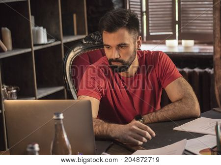 New projects. Young business man with beard sitting at table with laptop in cozy dark office and looks at proposals from potential business partners. Creative startup in studio