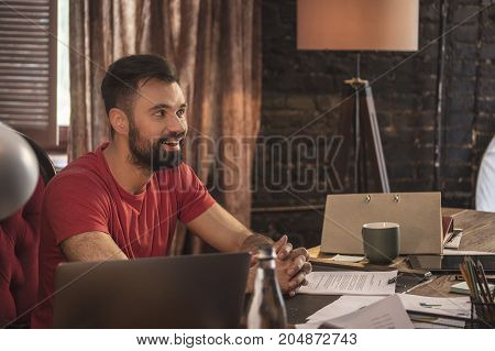 Creative head. Young business man sitting in start up cozy dark studio at wooden table with tablet and laptop and think about genius idea that came to mind