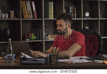 Serious approach to business. Young businessman sitting behind desk with documents and writing on laptop in cozy dark office. Creative startup in studio