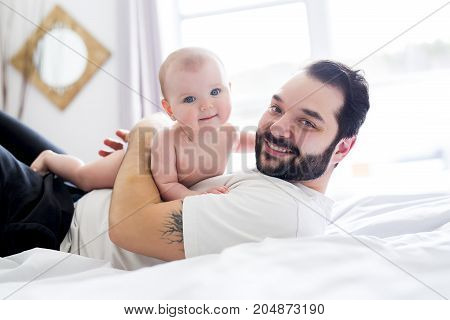 A Young happy father playing with babyon bed