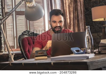 Taste of victory. Young businessman sitting in cozy office on soft chair with laptop and rejoices good news. Creative start up business in dark office