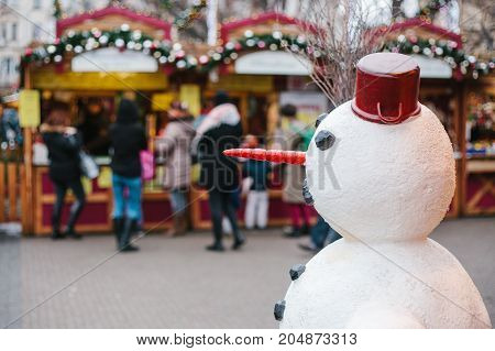 Snowman in the foreground, in the background Christmas market. Conceptual photo of the celebration of Christmas. Concept of the holiday.