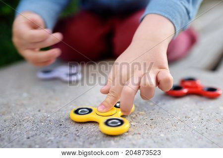 Child Playing With Popular Rotating Fidget Spinners