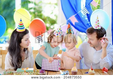 Cute little children twins and their parents having fun and celebrate birthday party with colorful decoration. Family with sweets candy whistle/blower/horn and festive gifts. Kid birthday party.
