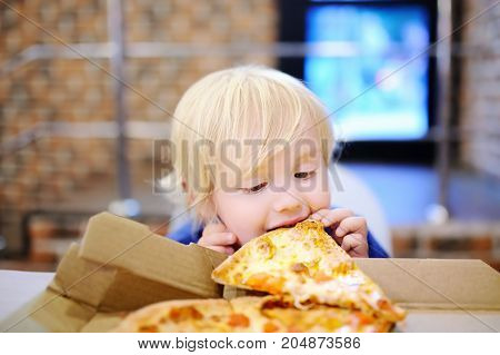 Cute Blonde Boy Eating Slice Of Pizza At Fast Food Restaurant