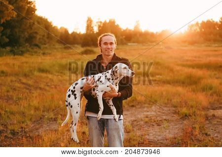 Happy man holding a big spotted dalmatian dog in hands smiling and looking at camera. Yellow grass and sunset on the background.