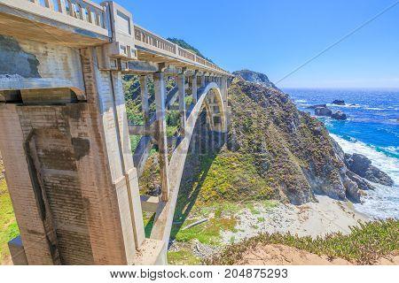 California travel concept. Iconic Bixby Creek Bridge on Pacific Coast Highway 1. Bixby Bridge is located near collapsed Pfeiffer Canyon Bridge in Big Sur.Popular landmark in California, United States.