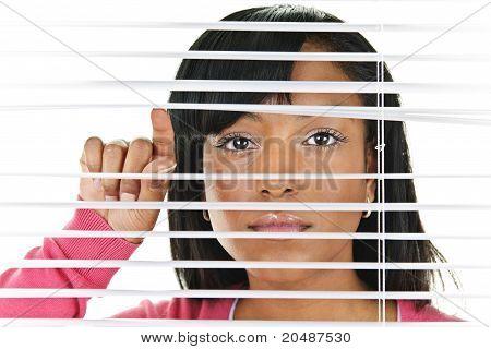 Mujer mirando a través de las persianas venecianas