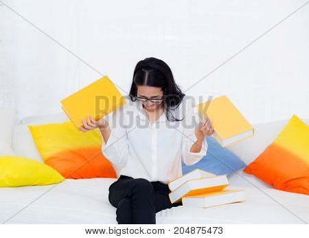 portrait of a beautiful young female student with not want read book on sofa in living room - education concept.