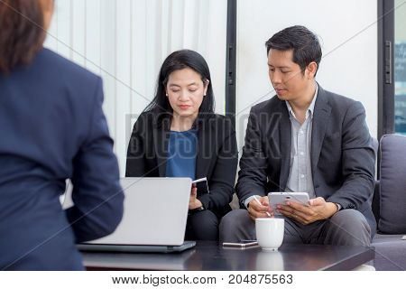 Team of business three people working together on a laptop with during a meeting sitting around a table.