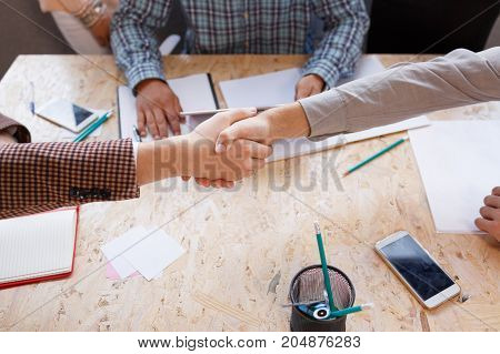 Business partners come to an agreement and shake hands.