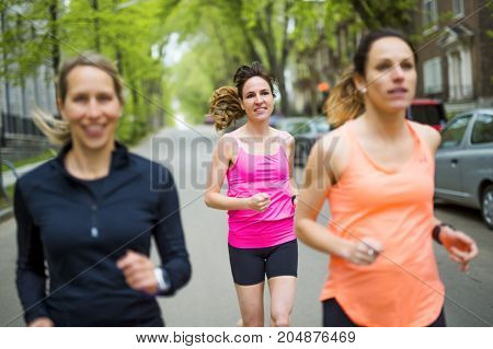 A group of people enjoying in the fitness having fun running outside