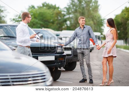 A young guy with a girl walks in the parking lot and chooses a car.