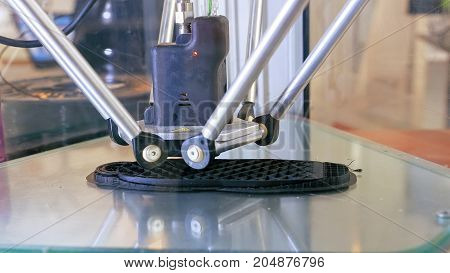 3D printer performs product creation. Modern 3D printing or additive manufacturing and robotic automation technology. Three dimensional printing is a new era in industrial design and production.