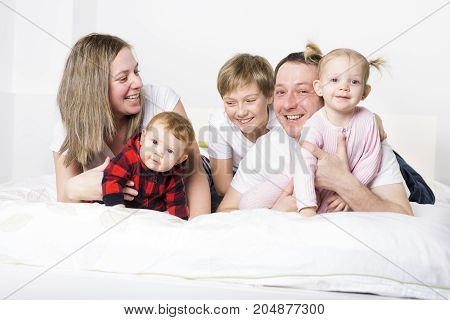 A five member Young Family Having Fun In Bed