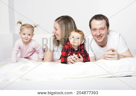 A family of four people cheerfully spends time for beds