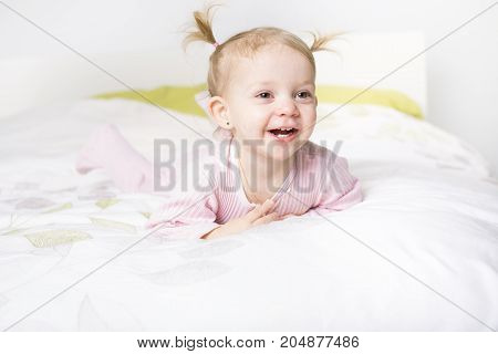A two year old blond girl in bed at home