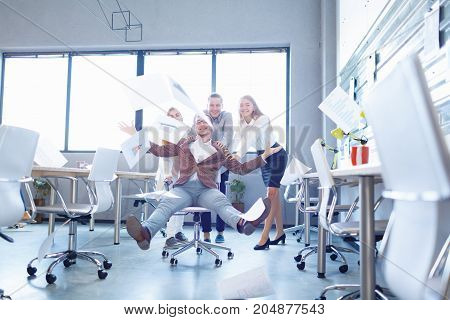 Excited, laughing office staff throwing paper in the air on a blurred room background. Happy boss throwing away documents.