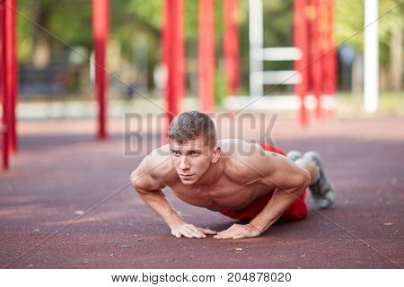 Attractive young male doing push-ups on a blurred playground background. A sporty male student with perfect biceps. Copy space.