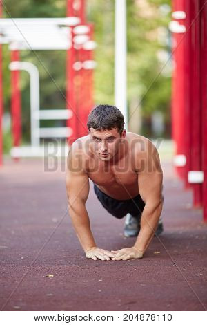A sexy shirtless young man doing a workout on a stadium area background. Fit guy doing push-ups outdoors. Copy space.