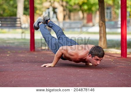 Healthy, sporty, hot young man doing pushups on a blurred stadium area background. Concentrated bodybuilder exercising.