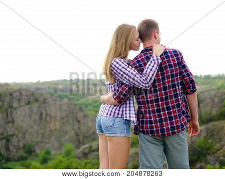 A sensual, romantic young couple on a blurred natural background. Cute girlfriend and confident boyfriend on a camping trip. Copy space.