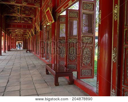 Hue, Vietnam - September 13 2017: Beautiful red wooden hall with golden ornate details in Hue citadel, Vietnam, Asia. Famous destination for tourists. UNESCO Heritage site.