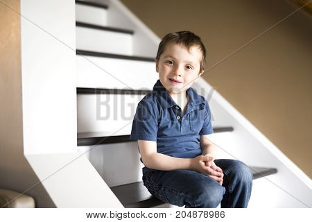 little boy sitting on the stairs in house at the day time.