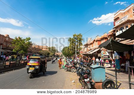 JAIPUR RAJASTHAN INDIA - MARCH 11 2016: Horizontal picture of tuk tuk driving in the street of Jaipur known as pink city of Rajasthan in India.