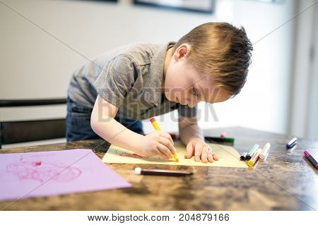 A Young Boy Drawing on the kitchen table
