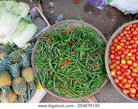 Close up of chili peppers, tomatoes, pineaples and some lettuce at outdoors in the street market in Hue, Vietnam.