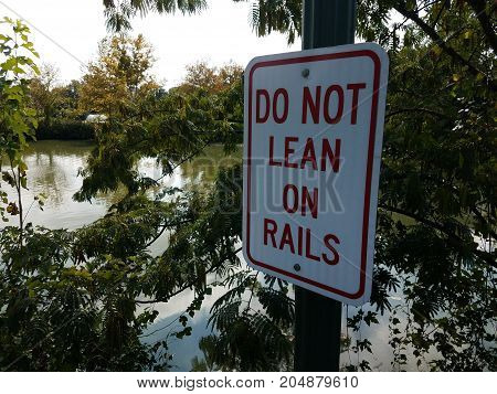 do not lean on rails sign on rail with water