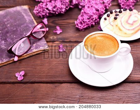 espresso in a white round cup with saucer on a brown table side closed book and glasses