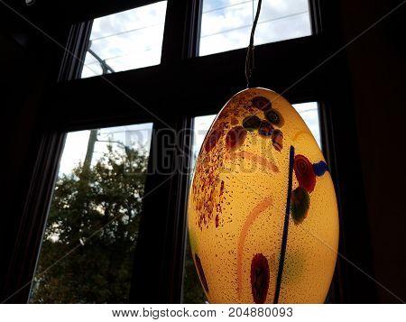 a colorful oval class light near a window