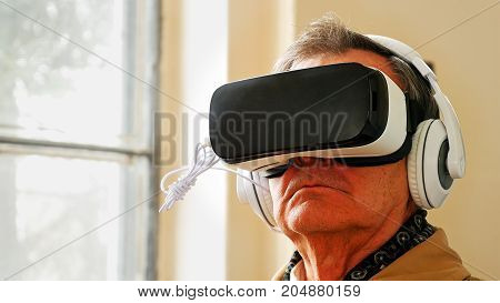 Senior old man wearing VR headset and enjoying virtual reality digital world. Virtual and augmented reality are increasingly used in human lives.
