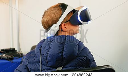 Child in VR headset enjoying virtual reality digital world. Virtual and augmented reality are increasingly used in human lives.