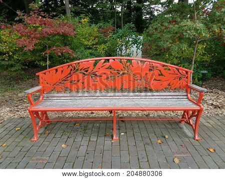 a red metal bench with leaves on bricks