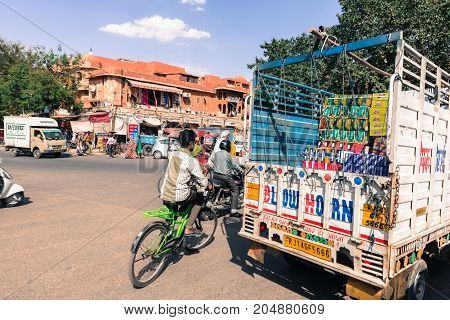 JAIPUR RAJASTHAN INDIA - MARCH 11 2016: Horizontal picture of bicycle motorcycle and truck sharing the same street in Jaipur known as pink city of Rajasthan in India.