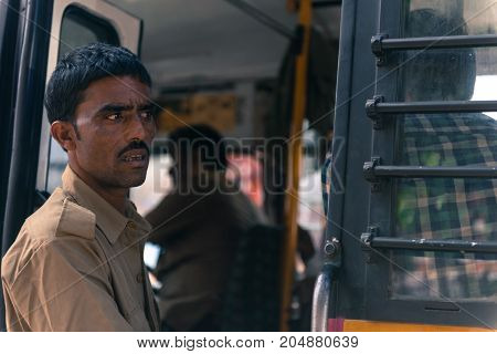 JAIPUR RAJASTHAN INDIA - MARCH 11 2016: Horizontal picture of indian black skin man looking from the bus in Jaipur known as pink city of Rajasthan in India.
